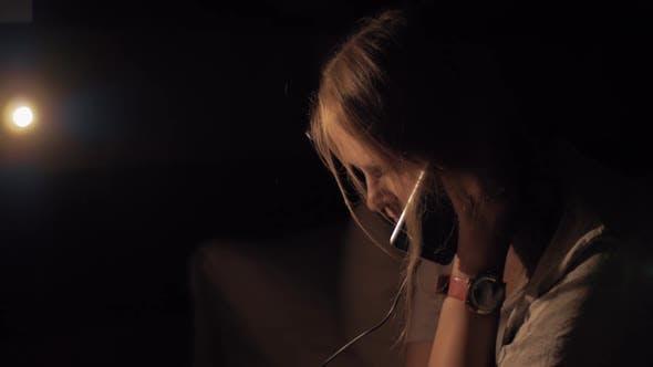 Woman in Dark Room Talking on Charging Mobile