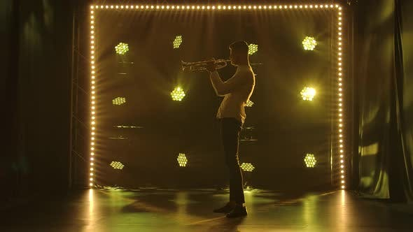 Thumbnail for Side View of a Man Playing the Trumpet Enthusiastically. Male Silhouette on a Dark Background with