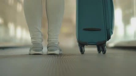 Thumbnail for Woman with a suitcase on a moving walkway, escalator, slow motion
