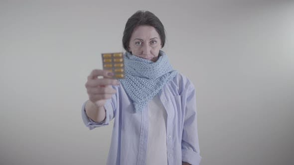 Thumbnail for Portrait of Adult Caucasian Woman Holding Blurred Blister Pack of Pills. Brunette Lady Showing