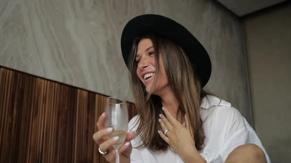 Cheerful Girl in a Hat Laughs and Drinks Champagne Sitting on the Bed