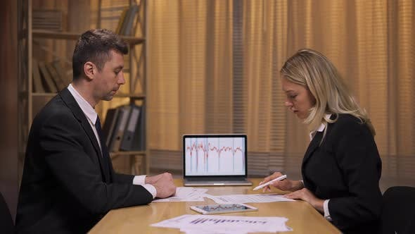 Business Partners Analyze Stock Market and Team Strategy in an Office Meeting