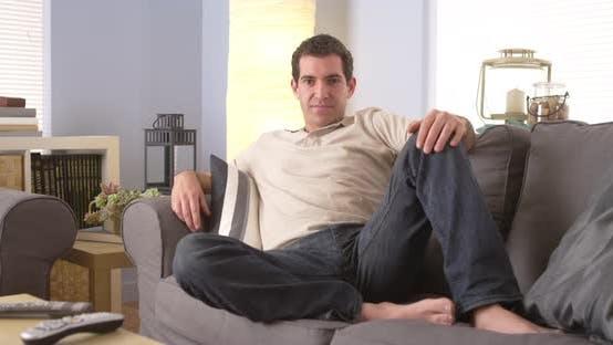 Thumbnail for Man lounging on sofa