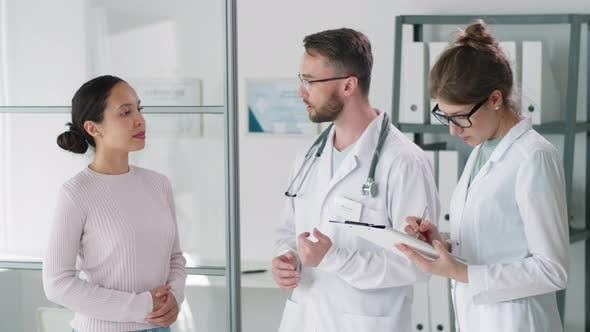 Thumbnail for Male Doctor Talking to Woman while His Female Assistant Taking Notes