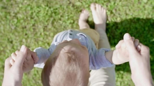 Thumbnail for POV of Woman Helping Toddler Walking on Grass