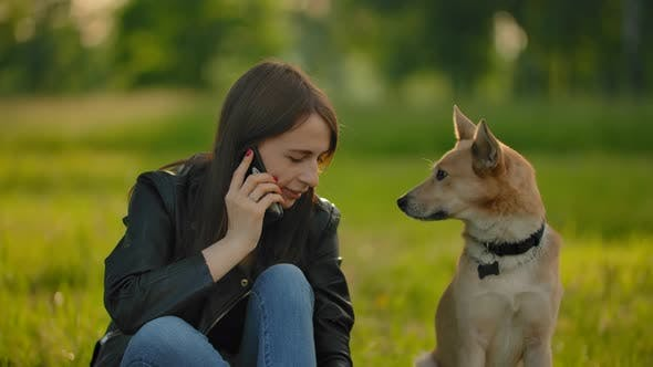 Thumbnail for Girl Talking on the Phone While Walking with a Dog in the Park.