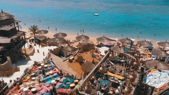 Thumbnail for Rocky Beach with Arabic Cafes in Retro Style on the Red Sea Coast with Umbrellas, Sun Beds and