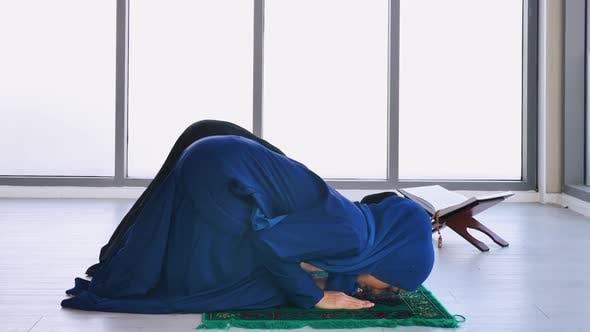 Muslim young women in traditional hijab are praying glorify Allah