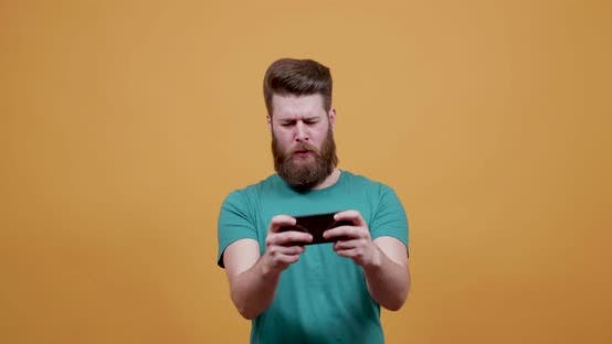 Thumbnail for Young Attractive Man Plays an Entertaining Game on His Smartphone