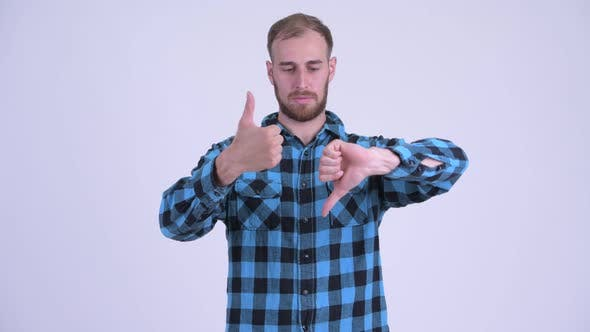 Thumbnail for Confused Bearded Hipster Man Choosing Between Thumbs Up and Thumbs Down