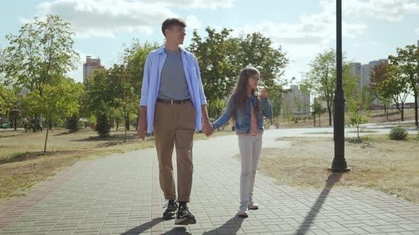 Thumbnail for Junger Bruder mit Hipster Outfit und seine niedliche kleine Hand halten und gehen in park