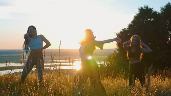 Aerobics in Nature - Three Young Women Doing Aerobic Dance and Slow Movements with Their Hands on