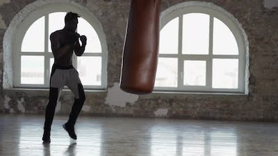 Shirtless Male Boxer Enjoying Training at Boxing Studio with Wrapped Hands