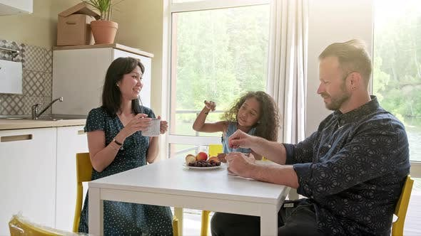 Thumbnail for Beautiful Family with Kid Sitting at the Table Drinking Coffee at New Home Around Cardboard Boxes