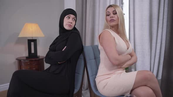 Thumbnail for Two Women Sitting Back To Back and Looking at Each Other. Muslim and Caucasian Ladies Depicting