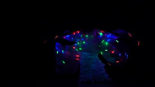 Belly Dancer Girl Dance with Two Glowing Lights Wings. Black Background. Sihouette