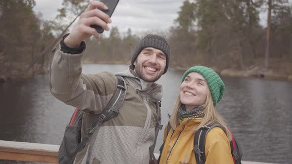 Thumbnail for Young Couple of Travelers Taking Selfie While Standing on a Bridge Against the Background of a Small
