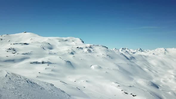 Thumbnail for Aerial drone view of snow covered mountains in the winter.