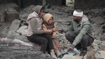 Refugees Sitting in Ruins of Demolished House