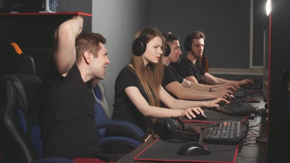 Team of Gamers Emotionally Rejoices in Victory Playing in E-sport Club
