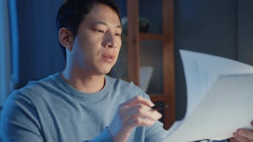 Asian freelance businessman focus work type on laptop computer busy with full of paperwork chart..