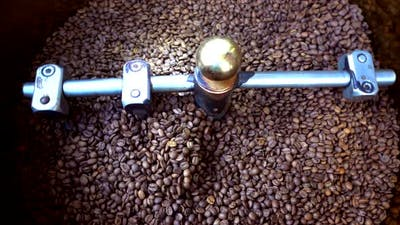 Mixing roasted coffee beans in roaster machine