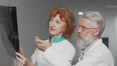 Two Experienced Senior Doctors Discussing MRI Scan of a Patient
