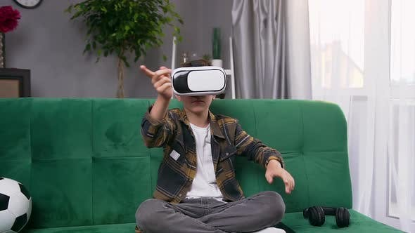 Thumbnail for Modern Teen Boy Sitting on Soft Green couch and Using Special Futuristic 3d Glasses to Play