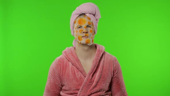 Thumbnail for Transsexual Man in Bathrobe with Face Mask Waves His Hand, Giving Thumbs Up
