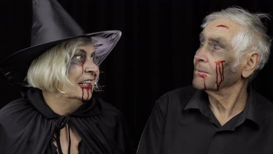 Ältere Mann und Frau in Halloween-Kostümen machen einen Kuss. Hexe und Zombie