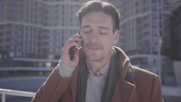 Thumbnail for Portrait of Handsome Confident Man in Brown Coat Standing in the City Street Talking By Cell Phone