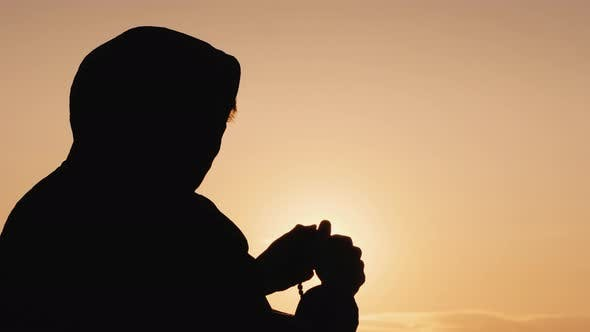 Thumbnail for Silhouette of a Man in the Hood, Sifting Through the Rosary at Sunset
