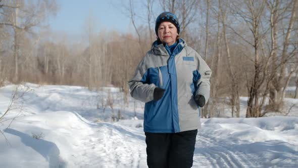 Thumbnail for Portrait of mature woman running in the winter forest