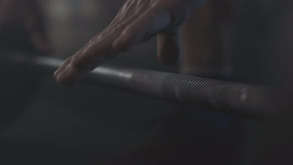 Thumbnail for Unrecognizable Sportsman Taking Barbell in Foggy Gym. Strong Male Hands Raising Hand Weights