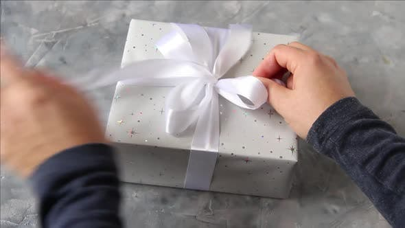 Thumbnail for Hands untie a bow on a present on a table