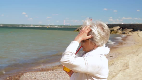 Cover Image for Senior Woman Drinking Shake on Summer Beach