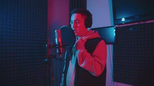 Ein Mann mit kurzen Haaren rapping im Studio