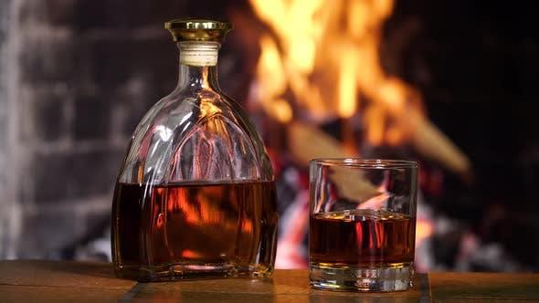 Flasche und Glas mit Whisky oder Cognac auf dem Hintergrund des Feuers im Kamin