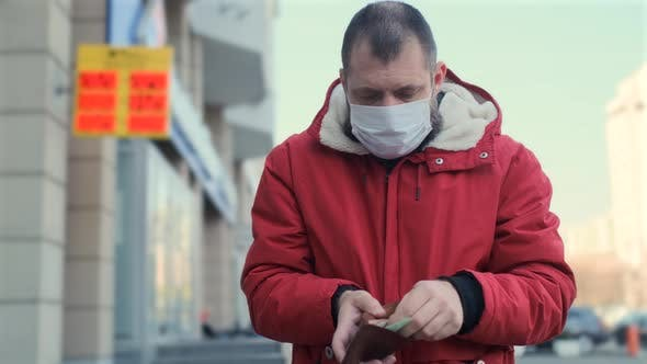 Thumbnail for Man Wearing Protective Face Mask Bankrupt Arrears Counting Banknotes in the Wallet. Currency