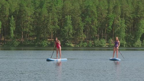 Sequence of Women Doing Sup Surfing
