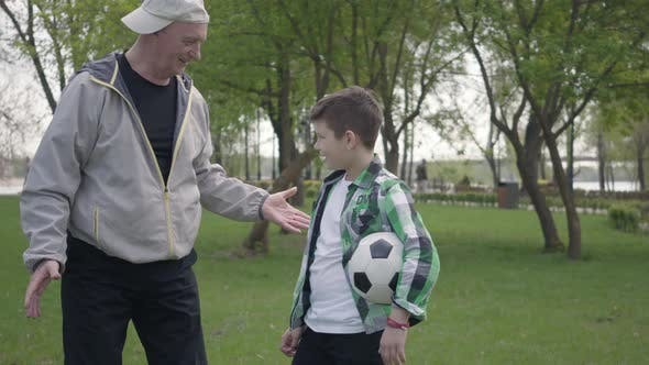 Thumbnail for The Little Boy in a Checkered Shirt and Positive Old Man Finishing To Play Soccer in the Park