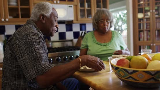 Thumbnail for Mature black couple eating lunch together in kitchen