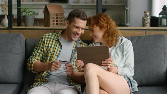 Thumbnail for Junges Paar genießt Online-Einkaufen, Mit Tablet-Computer, Sitzen auf Sofa