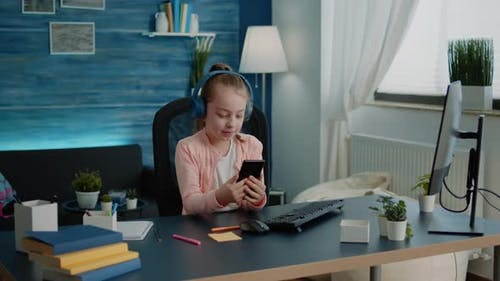 Little Girl Using Smartphone for Lessons on Video Call