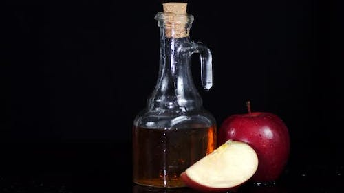 Apple Cider Vinegar Is Rotating on a Wooden Table.