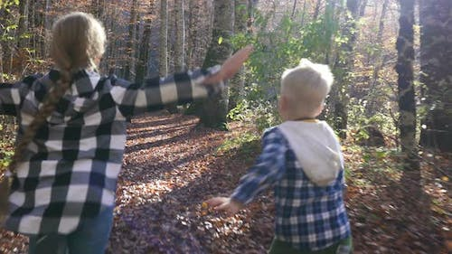 Little Carefree Children Happily Running Along the Forest Path with Both Their Arms Stretched Wide