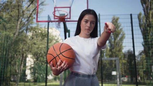 Attraktive Brünette Frau mit einem Basketballball herausfordernde Betrachter zeigt Ihr Finger
