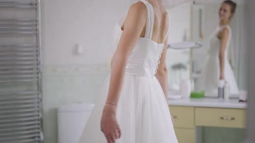 Unrecognizable Slim Happy Young Bride Spinning in Slow Motion in White Wedding Dress with Blurred