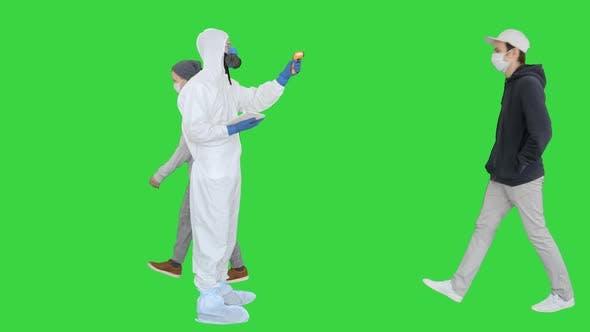 Mann im Gefahrgutanzug, der die Temperatur überprüft und die Frau auf einem grünen Bildschirm stoppt, Chroma Key.