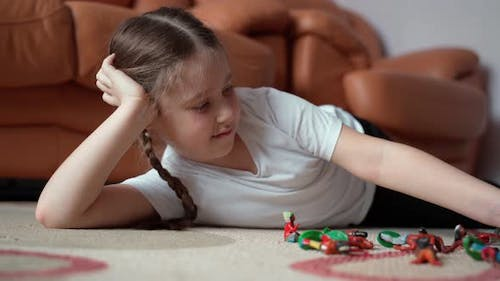 Girl with pretty face school age playing toy soldiers at home indoors. Close up shot